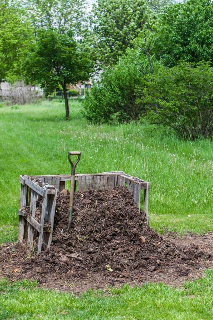 A small compost pile with a shovel on it on the backyard