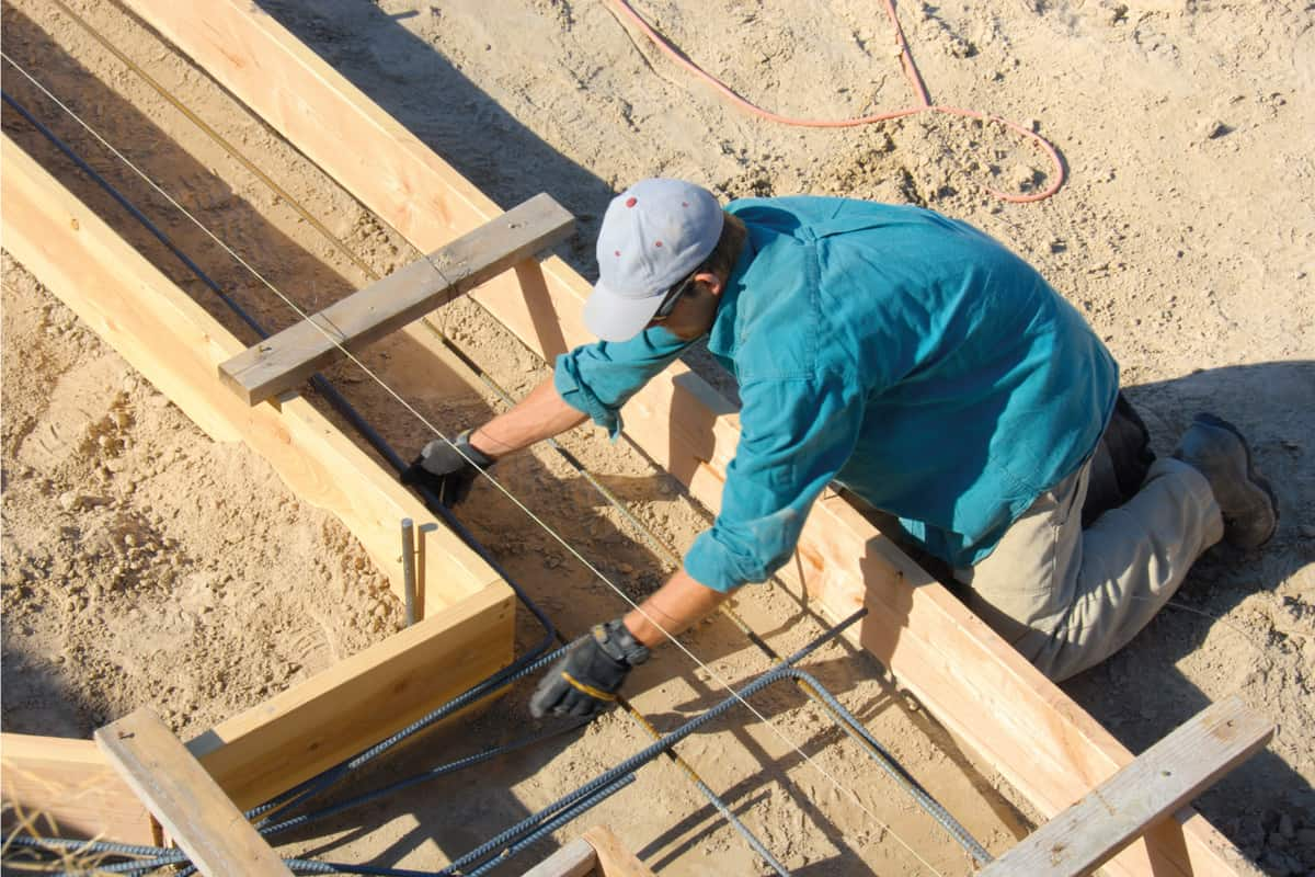 Carpenter placing the rebar in newly constructed footing frame. Preparing to pour concrete.