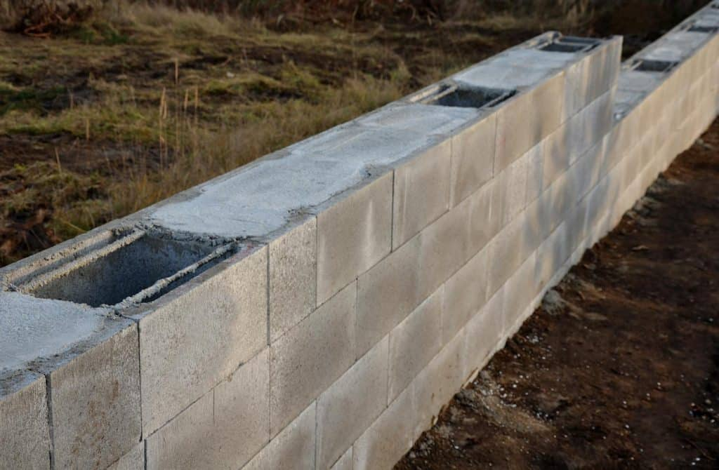 Construction of a concrete wall from concrete blocks filled inside with reinforcing steel and concrete