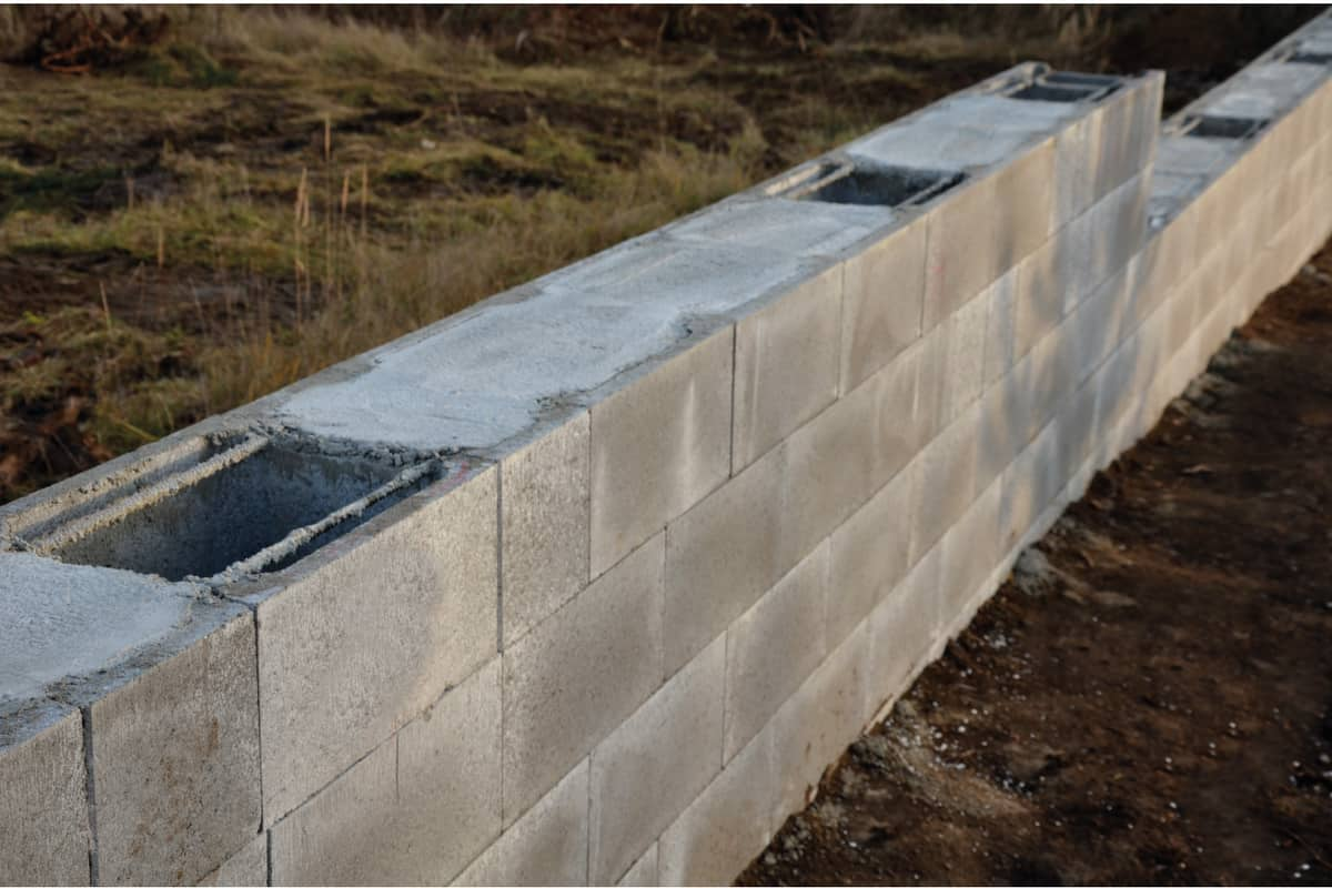 Construction of a concrete wall from concrete blocks filled inside with reinforcing steel and concrete. gray stepped wall