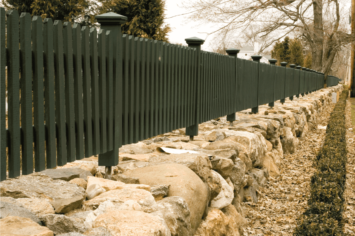 Long retaining wall and wood picket fence