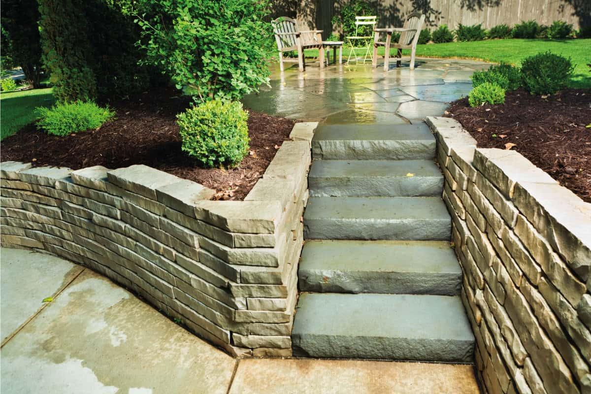 Lush, formal garden grounds design features trees, bushes, natural paver brick stones, layered rock surrounding retaining walls