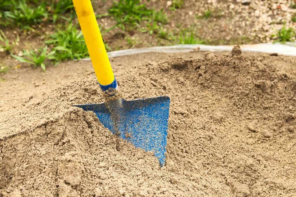 Physical work of loading sand into wheelbarrow