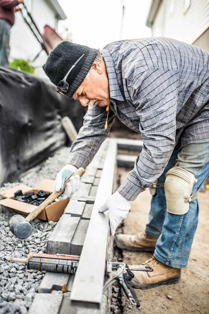 Senior man building a retaining wall with concrete blocks
