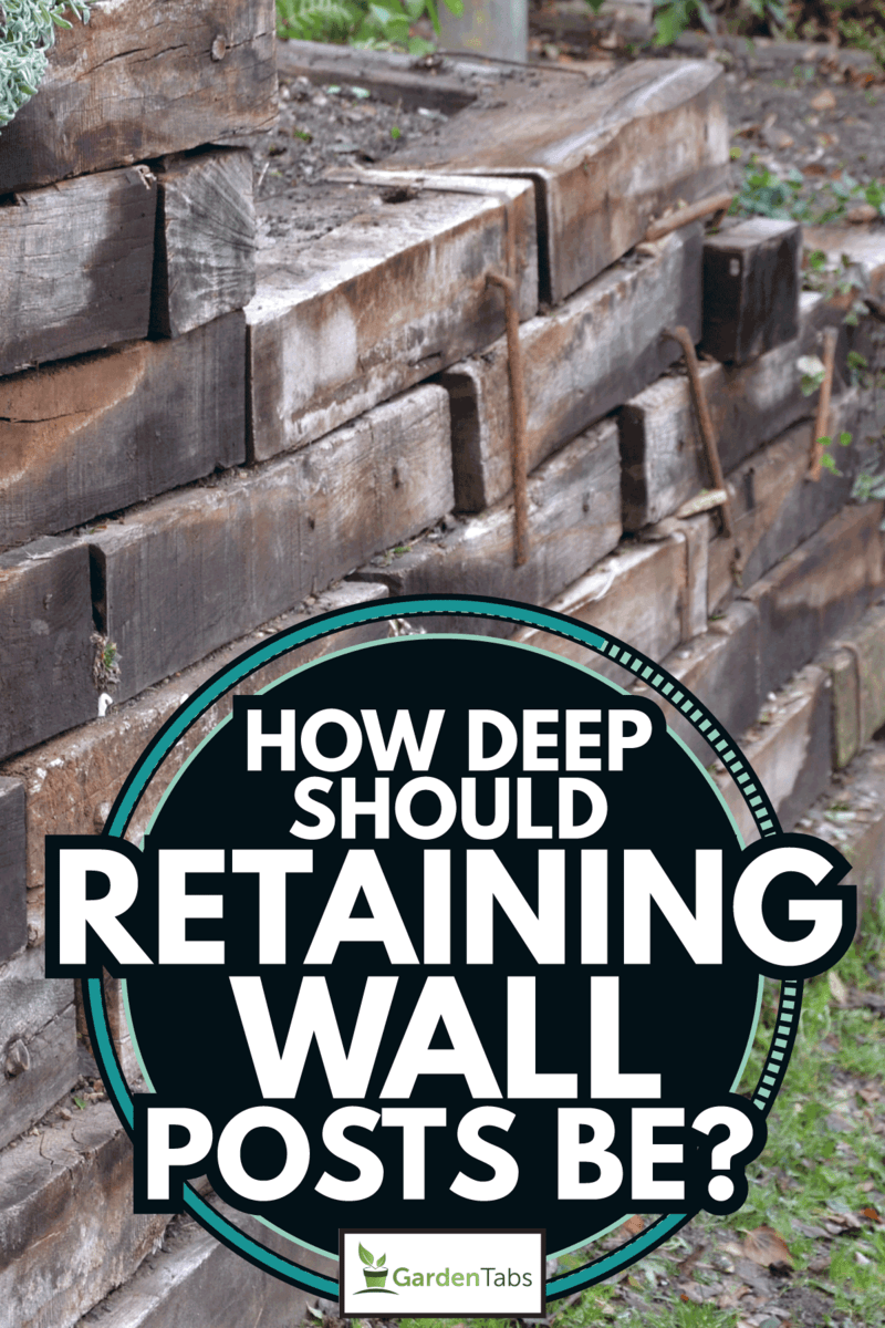 The retaining wall made of wooden sleepers is wooden and forms the edge of the perennial flowerbed. How Deep Should Retaining Wall Posts Be