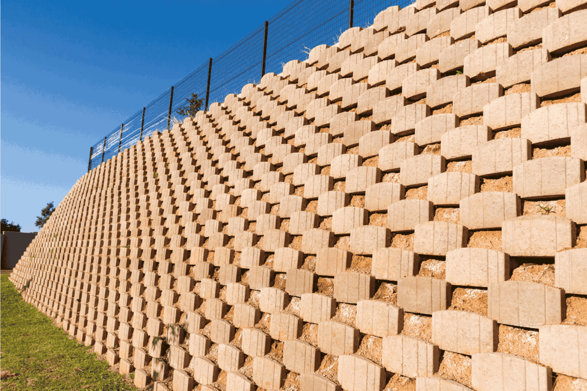 Wall retaining blocks bricks inter locking concrete products in construction with fencing on field plateau.
