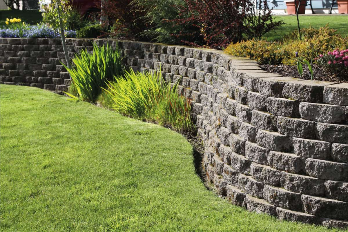 Well landscaped wall of cement cobblestone bricks with grass and ornamental plants. How Deep Should Retaining Wall Posts Be