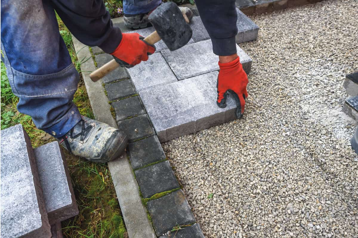hand with rubber hammer install paving block