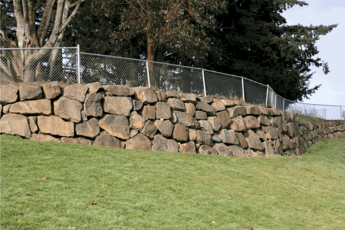 rock retaining wall with wire fence on top
